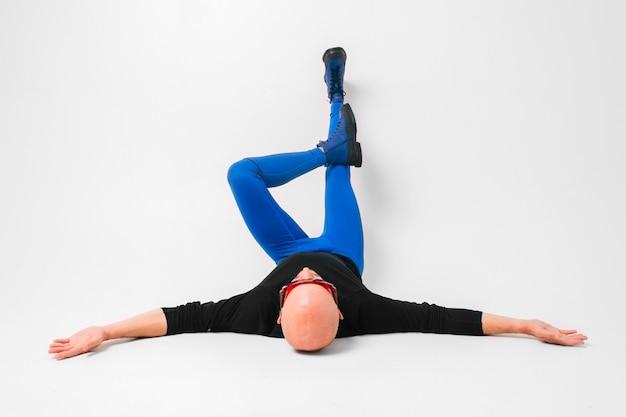 青いタイツと白いスタジオで組んだ足を離れて手で横になっているブーツでスタイリッシュなハゲ男の肖像