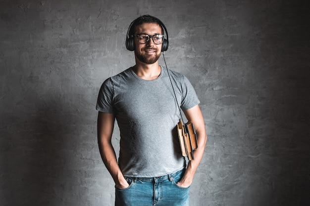 彼のイヤホンと灰色の背景にオーディオブックを聞いて灰色のカジュアルなtシャツに身を包んだスタイリッシュなひげを生やした男の肖像画