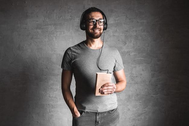 Портрет стильного бородатого мужчины, одетого в серую повседневную футболку, слушающего аудиокнигу в наушниках на сером фоне