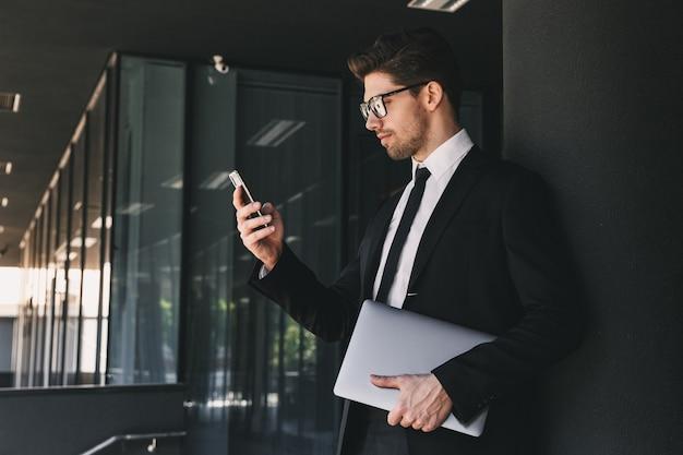 ノートパソコンでガラスの建物の外に立って、携帯電話を使用してフォーマルなスーツに身を包んだスタイリッシュなビジネスマンの肖像画