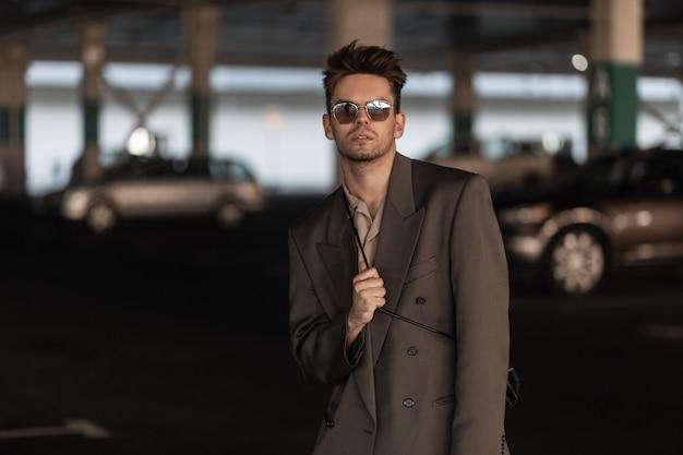 ファッショナブルなビジネスで髪型と無精ひげを持ったスタイリッシュなビジネスマンの肖像画は、駐車場でジャケットとシャツの衣装を見てください