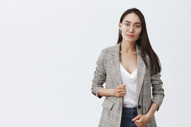 Портрет стильной женственной женщины в модном пиджаке и очках, вежливо улыбающейся и стоящей над серой стеной