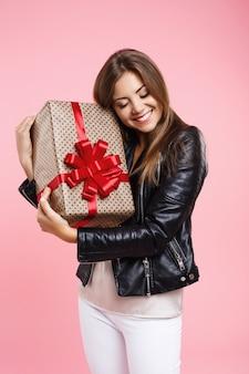 Портрет стильная девушка держит большой подарок на день рождения