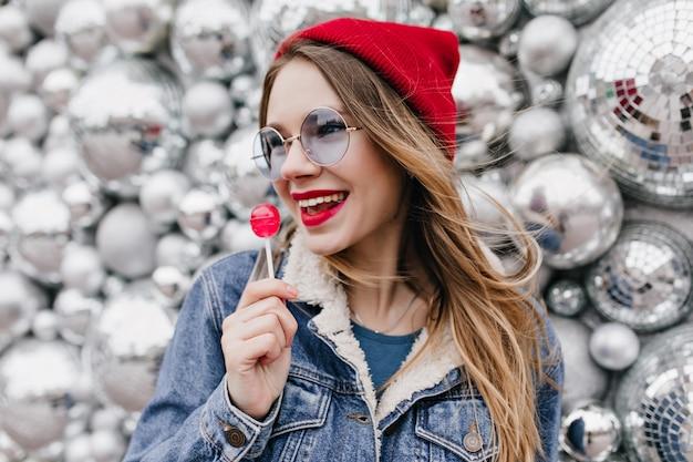 キャンディーを食べて目をそらすデニムジャケットのスタイリッシュな女の子の肖像画。光沢のある壁にロリポップでポーズをとる赤い帽子と丸いメガネの素晴らしいヨーロッパの女性。