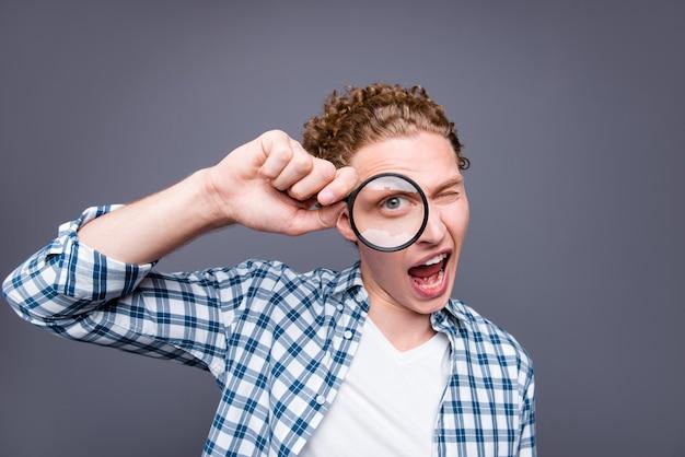 루페를 찾고 캐주얼 체크 무늬 셔츠 한쪽 눈에 세련된 남자 물결 모양의 머리의 초상화