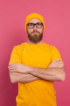 Портрет стильного красивого европейского бородатого мужчины в повседневной желтой рубашке, шляпе и очках на розовом фоне