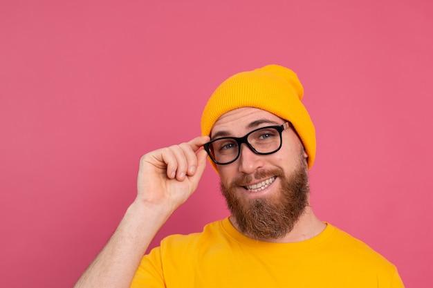 Портрет стильного красивого европейского бородатого мужчины в повседневной желтой рубашке, шляпе и очках на розовом