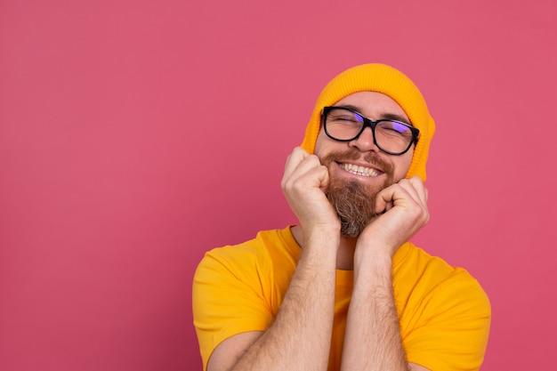 캐주얼 노란색 셔츠 모자와 분홍색 안경에 세련된 잘 생긴 유럽 수염 난된 남자의 초상화