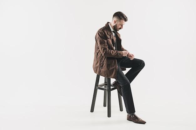 白に対してスタジオに座っているスタイリッシュなハンサムな若い男の肖像画。ジャケットを着た男