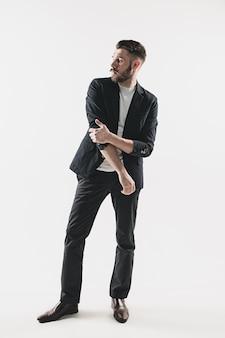 白に対して立っているスタイリッシュなハンサムな若い男の肖像画。ジャケットを着た男
