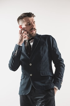 白に対してスタジオに立っているスタイリッシュなハンサムな若い男の肖像画。ジャケットを着た男