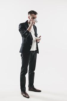 Портрет стильного красивого молодого человека, стоящего в студии.