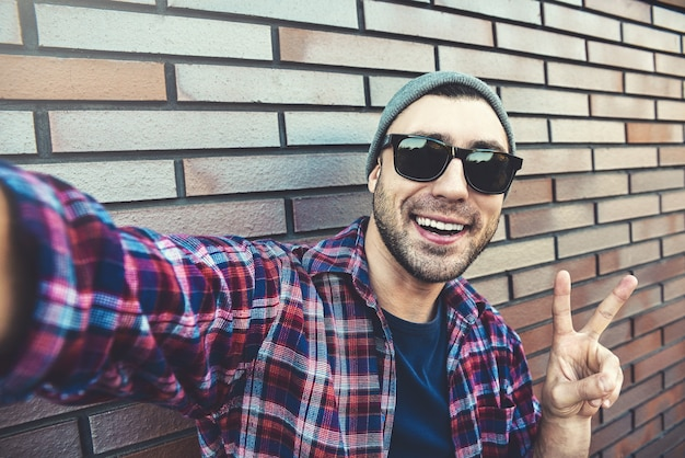 Портрет стильного красивого молодого человека с щетиной, стоящей на открытом воздухе и опирающейся на кирпичную стену. человек в солнцезащитных очках и шляпе. человек делает селфи.