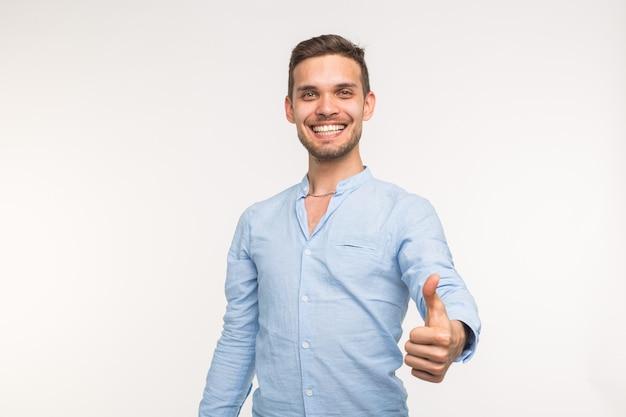 白い背景で隔離の親指を上にスタイリッシュなハンサムな若い男の肖像画。