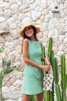 白い石の壁とサボテンの背景に麦わら帽子をかぶってバッグを保持しているエレガントな夏の緑のドレスでスタイリッシュな幸せなかわいい笑顔の女性の肖像画