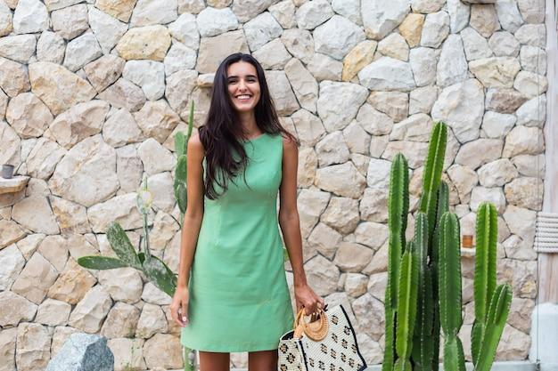 흰 돌 벽과 선인장의 배경에 밀짚 모자를 쓰고 가방을 들고 우아한 여름 녹색 드레스에 세련 된 행복 귀여운 웃는 여자의 초상화