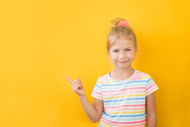 Портрет стильной маленькой девочки с пальцем вверх. у маленького ребенка в полосатой рубашке есть идея. малыш, изолированные на желтой доске. успех, яркая идея, креативные идеи и концепция инновационных технологий