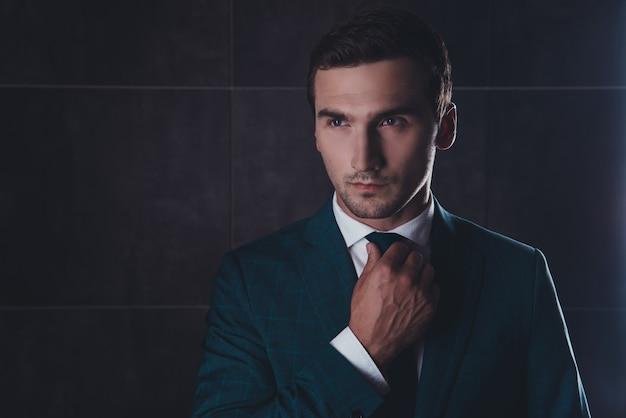 ネクタイを修正する黒のスーツのスタイリッシュな男の肖像画