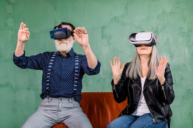 スタイリッシュなモダンな高齢者の男性と女性、トレンディな服を着て、仮想現実ゴーグルで赤い椅子に座って、空気中の架空の画面に触れるの肖像画 Premium写真