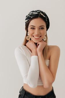 白い壁の上のカメラでポーズをとって頭に白いトップ、ジュエリー、ショールを身に着けているスタイリッシュな現代女性の肖像画