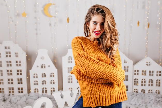 Портрет стильной, загадочной девушки 23 лет в горчичном теплом свитере. женщина с длинными волосами позирует