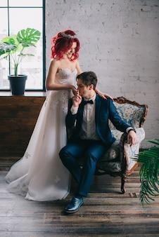 빈티지 의자에 앉아 세련된 신혼 부부의 초상화