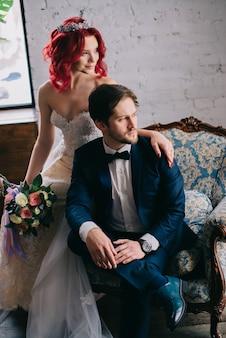 Портрет стильных молодоженов, сидящих в винтажном кресле
