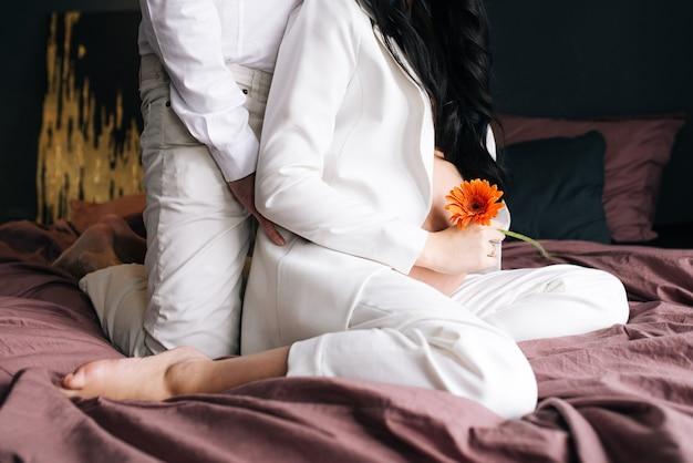 Крупным планом портрет стильной беременной женщины с цветами и живот