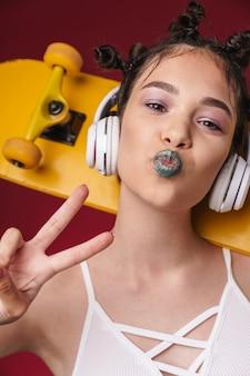 赤い壁に隔離されたヘッドフォンで音楽を聴きながら、奇妙な髪型とスケートボードを保持している暗い口紅を持つスタイリッシュなパンクの女の子の肖像画