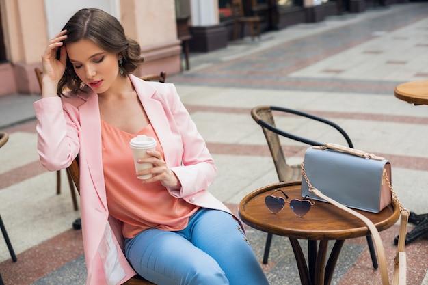コーヒーを飲み、アパレル、春夏のトレンド、ファッションアクセサリーサングラスとバッグでピンクとブルーの色を身に着けているカフェに座っているスタイリッシュなロマンチックな女性の肖像画