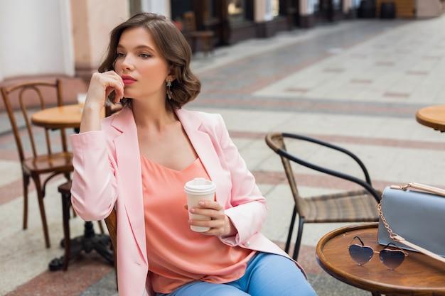 コーヒーを飲みながら、ピンクのジャケットとブラウスを着て、アパレルの色のトレンド、春夏のファッション、アクセサリーのサングラスとバッグ、考えて、見て、カフェに座っているスタイリッシュなロマンチックな女性の肖像画