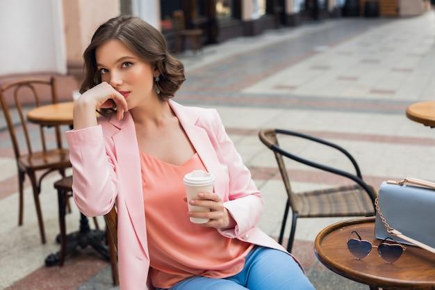 コーヒーを飲みながら、ピンクのジャケットとブラウスを着て、アパレルの色のトレンド、春夏のファッション、アクセサリーサングラスとバッグ、思慮深いカフェに座っているスタイリッシュなロマンチックな女性の肖像画