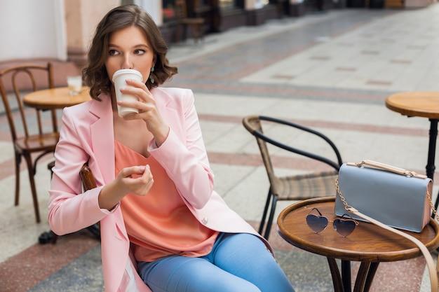 Портрет стильной романтичной женщины, сидящей в кафе, пьющей кофе, в розовой куртке и блузке, цветовых тенденциях в одежде, весенне-летней моде, аксессуарах, солнцезащитных очках и сумке