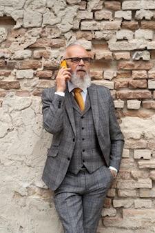 Портрет стильного старшего мужчины на своем телефоне