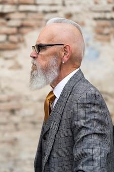 Портрет стильного старшего мужчины, сидящего