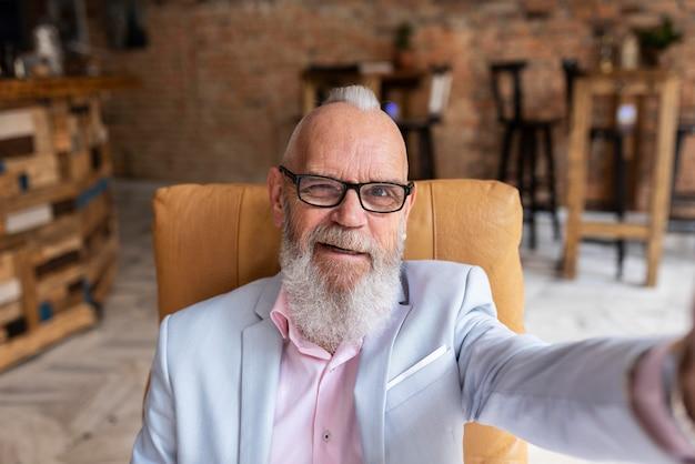 Портрет стильного старшего мужчины, делающего селфи