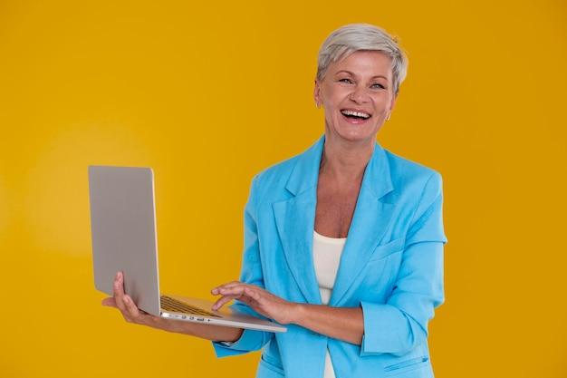 Портрет стильной старшей женщины, держащей ноутбук