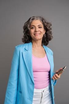 Портрет стильной старшей женщины, держащей ее телефон