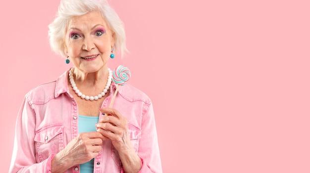 Портрет стильной старшей женщины в розовом
