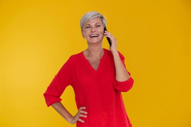 Портрет стильной старшей женщины разговаривает по телефону