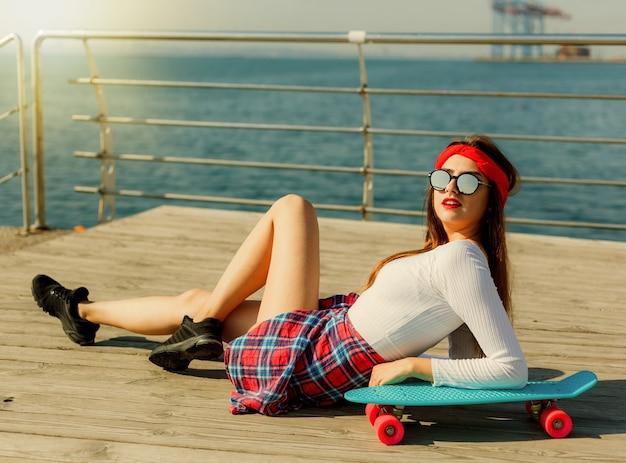 해변에서 세련 된 스케이팅 여자의 초상화입니다. 매력적인 섹시 한 여자 스케이트 야외에 누워
