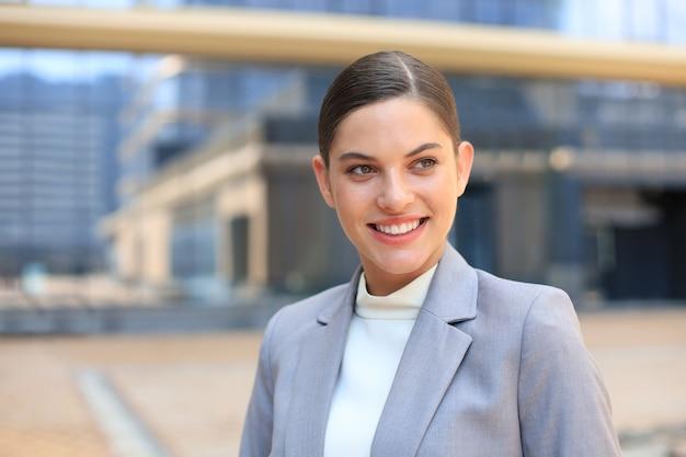 Портрет стильной улыбающейся деловой женщины в модной одежде в большом городе, целенаправленно глядя в сторону.