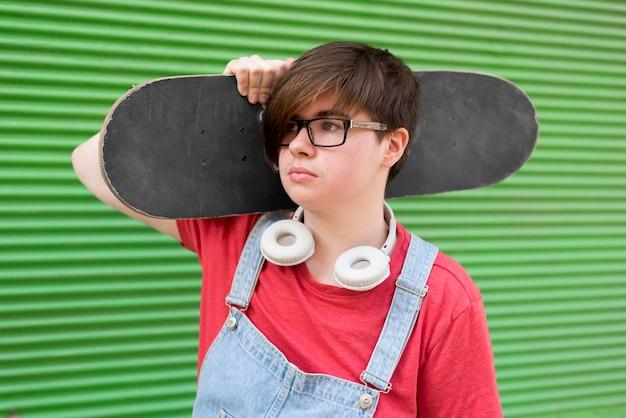Портрет стильный подросток держит скейтборд