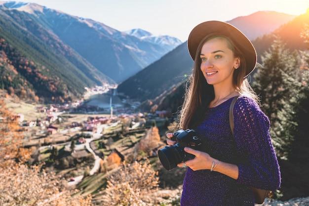 トルコ旅行中にトラブゾンの山とウズンゴル湖の写真を撮っている間にフェルト帽子のスタイリッシュなトレンディな流行に敏感な女性旅行者カメラマンの肖像画
