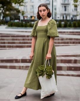 Портрет стильной женщины, несущей сумку с продуктами