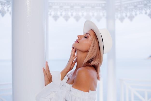 Портрет стильной женщины в объемном белом модном топе и классической роскошной шляпе