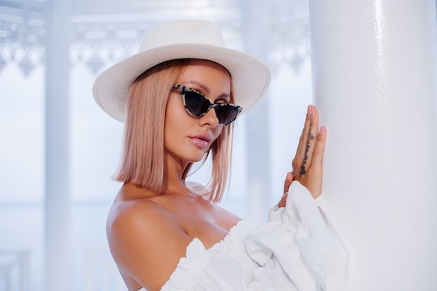 Портрет стильной женщины в объемном белом модном топе, солнцезащитных очках с леопардовым принтом и классической роскошной шляпе
