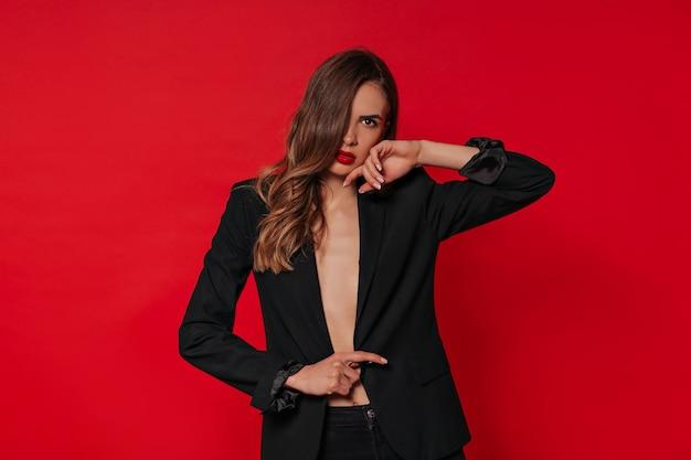 赤い壁に赤い唇でポーズをとって黒いジャケットを着ているスタイリッシュな女性の肖像画