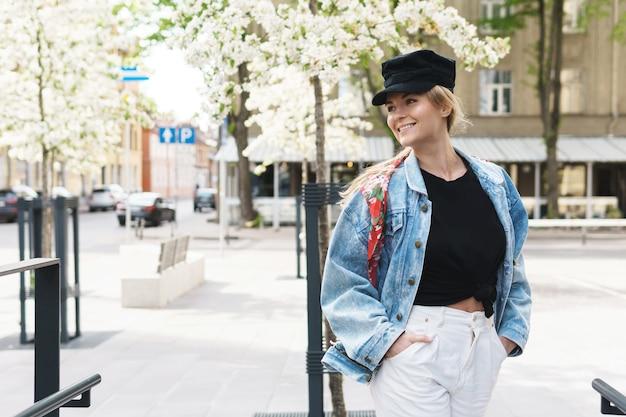 Портрет стильной женщины в джинсовой куртке и черной кепке