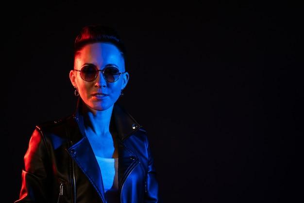 가죽 재킷에 짧은 머리를 하고 빨간색과 파란색 네온으로 둥근 안경을 쓴 세련된 여성의 초상화